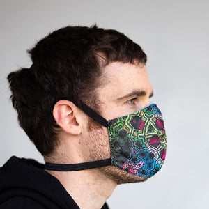 Purple and green fractal art print fabric mask, on face, side view.