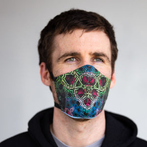 Purple and green fractal art print fabric mask, on face, front view.