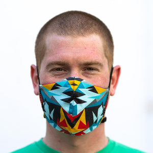 Triangular art print fabric mask, on face, front view.