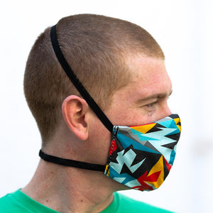 Triangular art print fabric mask, on face, side view.
