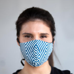 Blue Chevron art print fabric mask, on face, front view.