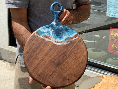 Beautifully crafted cutting board that is also a charcuterie board.  It has blue and white resin on the handle that leads into one side of the board.
