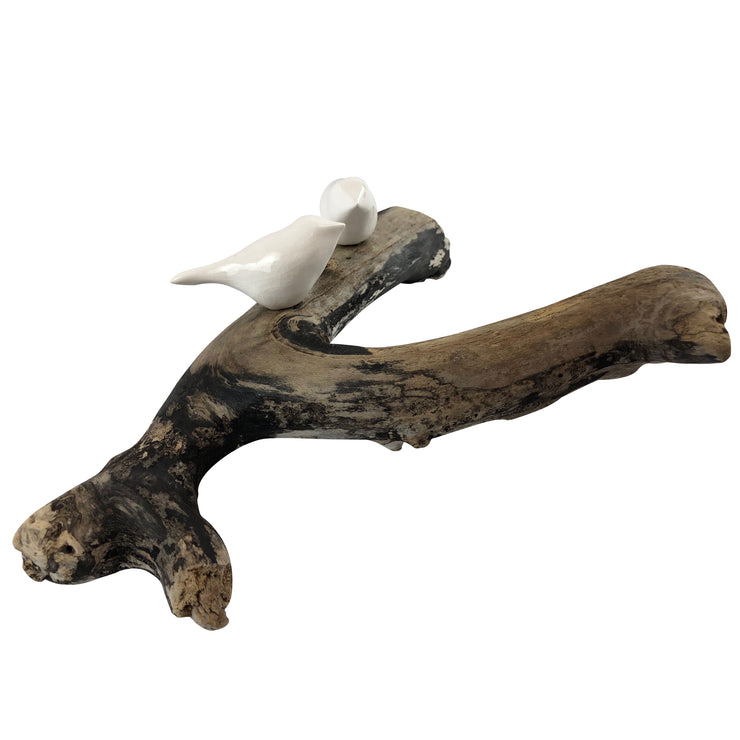 Two hand sculpted birds on driftwood