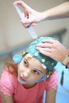 Doctor setting up EEG cap on pediatric patient