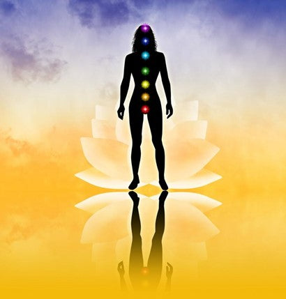 A woman's silhouette standing on a gradient background with a lotus flower, colored chakra balls highlighted on her body.