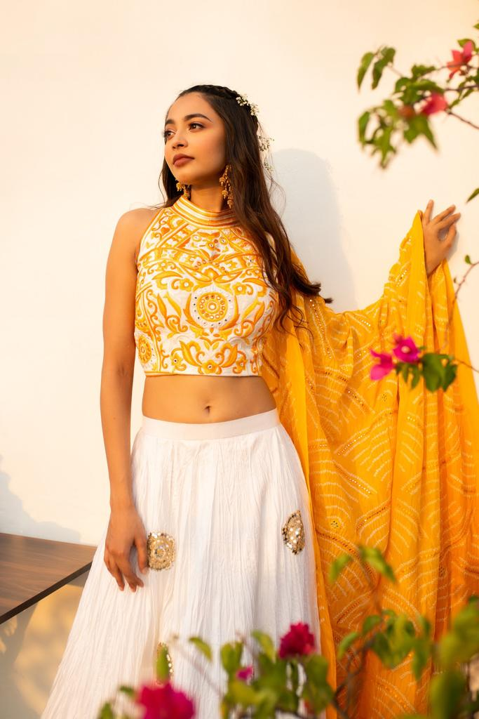 YELLOW AND IVORY LEHENGA SET WITH HAND EMBROIDERED MIRROR WORK EMBELLISHED HALTER NECK BLOUSE AND BANDHANI DUPATTA