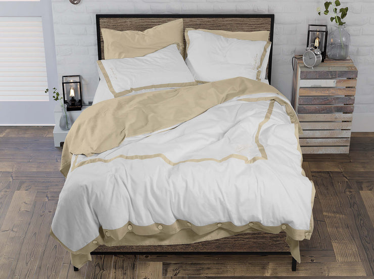 unmade bed with hotel style embroidered duvet set
