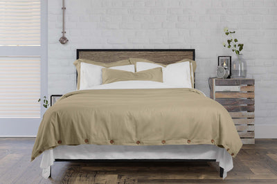neatly made bed with dune duvet cover and signature collection pillows