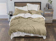 unmade bed with dune and white organic cotton luxury bedding