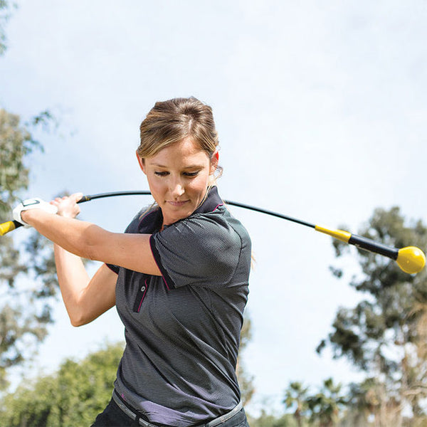 Woman practicing golf with SKLZ Gold flex golf swing trainer