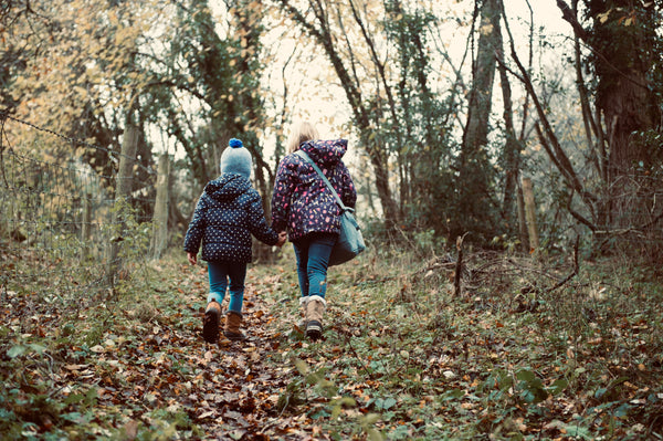 two children walk through the woods