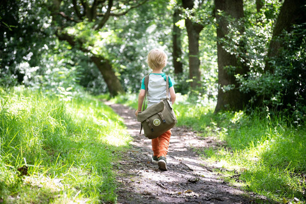 A child with a den kit on his shoulder walks into the woods to play with dens and nature