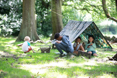 Children play into the woods with dens and nature