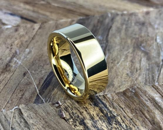 Gold tungsten men's engagement ring on wood