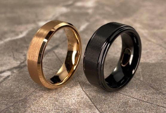 gold tungsten men's engagement ring and black tungsten engagement ring on tile background