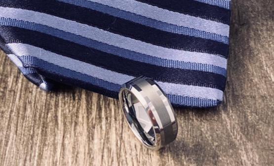 Silver men's comfort fit wedding band in front of blue tie.