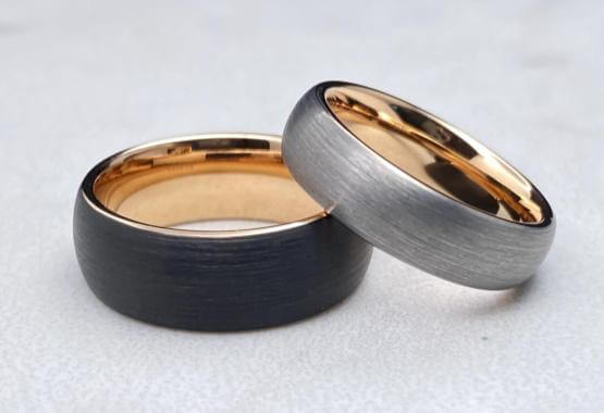 Two men's tungsten wedding bands with rose gold interiors