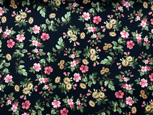 Black cotton fabric covered with pink and peach flowers and green leaves.