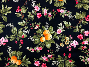 Black cotton fabric covered with flowers and fruit such as cherries.