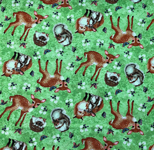 Green cotton fabric covered with deer squirrels and other animals.