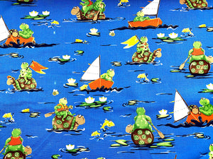 Cotton fabric covered with frogs and turtles paddling around in the water.