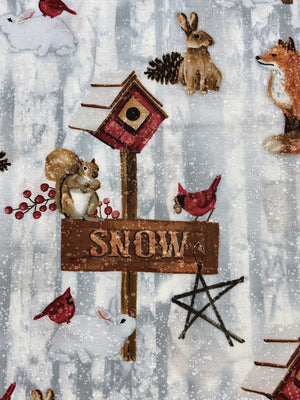 Close up of a snow sign on a bird house post with a squirrel and bird sitting on the sign.