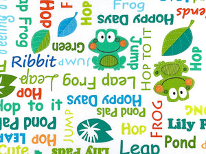 Close up of white cotton fabric covered with frogs and sayings.