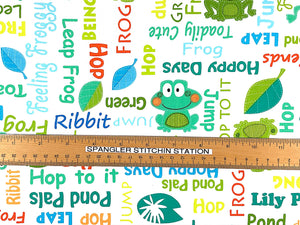 Ruler on white fabric that is covered with frogs and sayings.