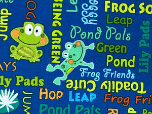 Close up of frogs and words on blue fabric.