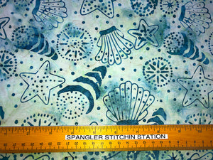 Ruler on fabric to show sizing of sea shells and star fish.