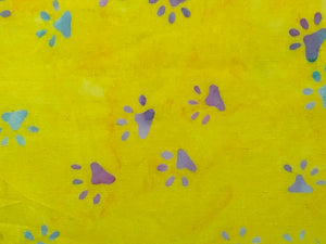 Close up of yellow batik fabric with shades of blue, green, pink and red paw prints.