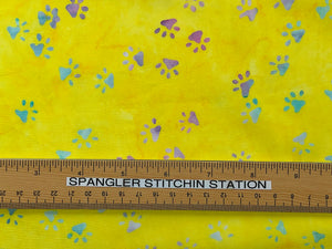 Yellow batik fabric covered in shades of blue, green, pink and red paw prints with ruler showing sizing.