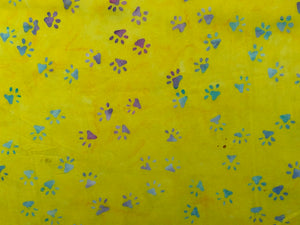 Yellow batik fabric covered in shades of blue, green, pink and red paw prints.