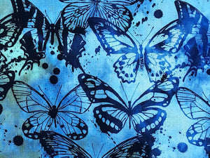 Close up of blue and green cotton batik fabric covered with butterflies.
