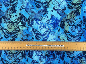 Ruler on blue and green cotton batik fabric covered with butterflies.
