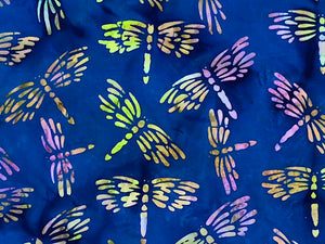 Close up of dragonflies on blue batik fabric.