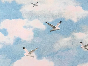 Close up of sky blue cotton fabric covered with birds and clouds.