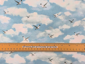 Ruler on sky blue fabric covered with birds and clouds.