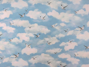 Cotton fabric covered with clouds and birds.