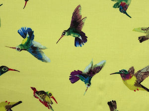 Close up of yellow cotton fabric covered with hummingbirds.