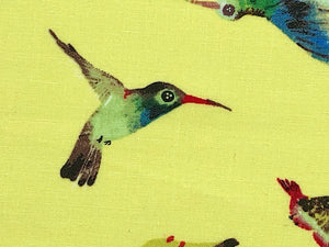 Close up of hummingbird on yellow cotton fabric.