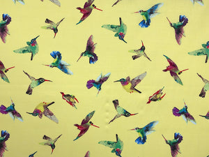 Yellow cotton fabric covered with hummingbirds.
