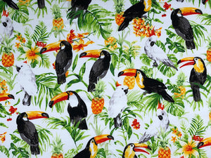 White cotton fabric covered with white Toucans, Parrots, flowers and pineapples.