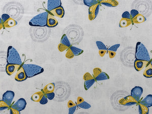 Close up of white cotton fabric with blue and yellow butterflies