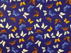 Cotton fabric covered with white, blue, yellow and orange butterflies.