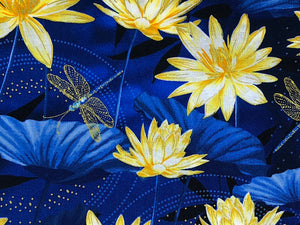 Close up of blue cotton fabric covered with water lilies and dragonflies.