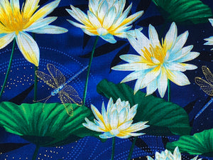 Close up of blue cotton fabric covered with water lilies and gold dragonflies.