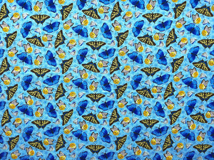 Blue fabric covered with blue, yellow, black and white butterflies.