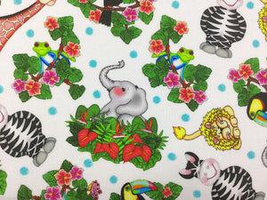 Close up of white cotton fabric with an elephant sitting in some plants.