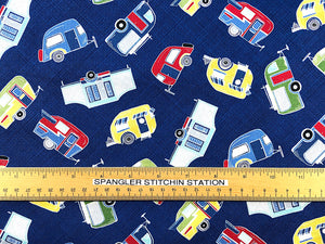 Ruler on blue fabric covered with tossed travel trailers.